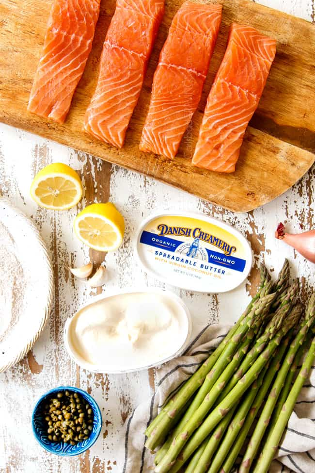 showing how to make salmon recipe by showing ingredients: salmon fillets on a cutting board, flour to dredge salmon in, butter, asparagus