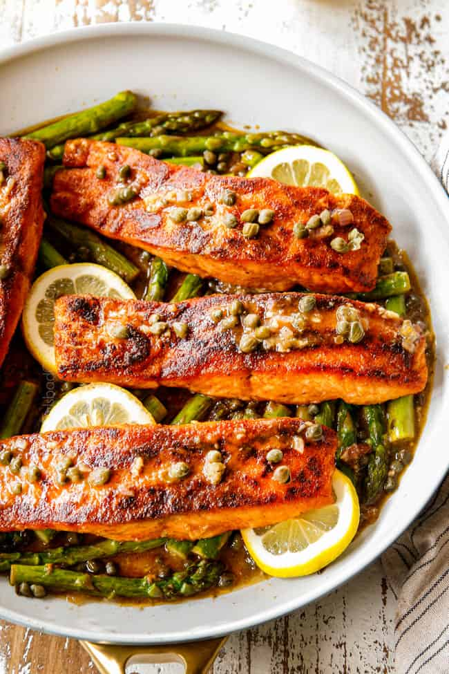showing how to make lemon salmon and asparagus recipe by by spooning piccata sauce over fish