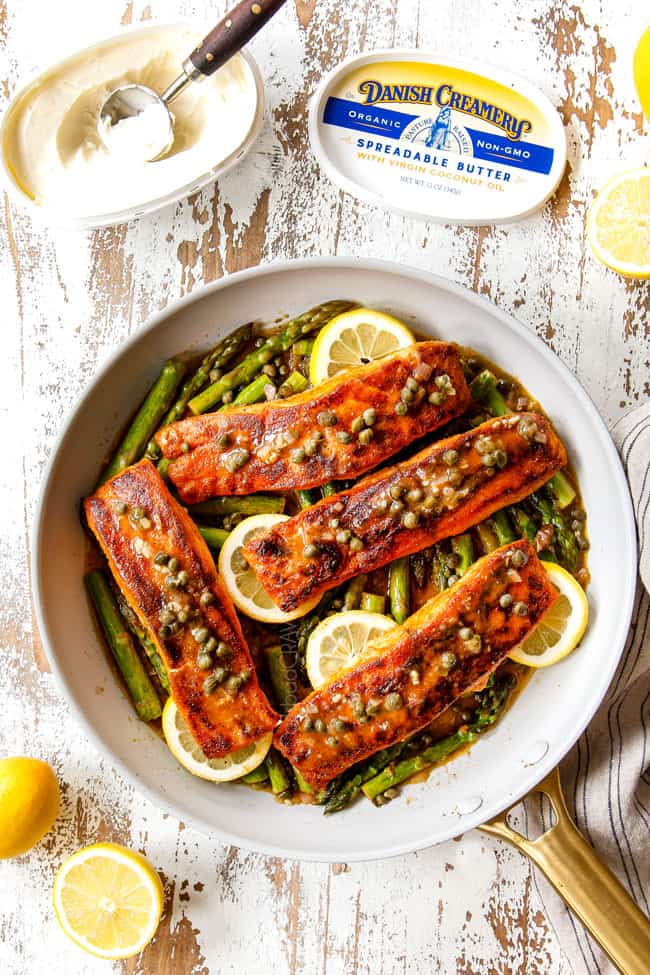 showing how to make lemon butter salmon and asparagus with a top view of salmon laying over asparagus in a pan