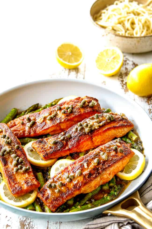 showing how to serve salmon and asparagus by serving in a pan over lemon slices