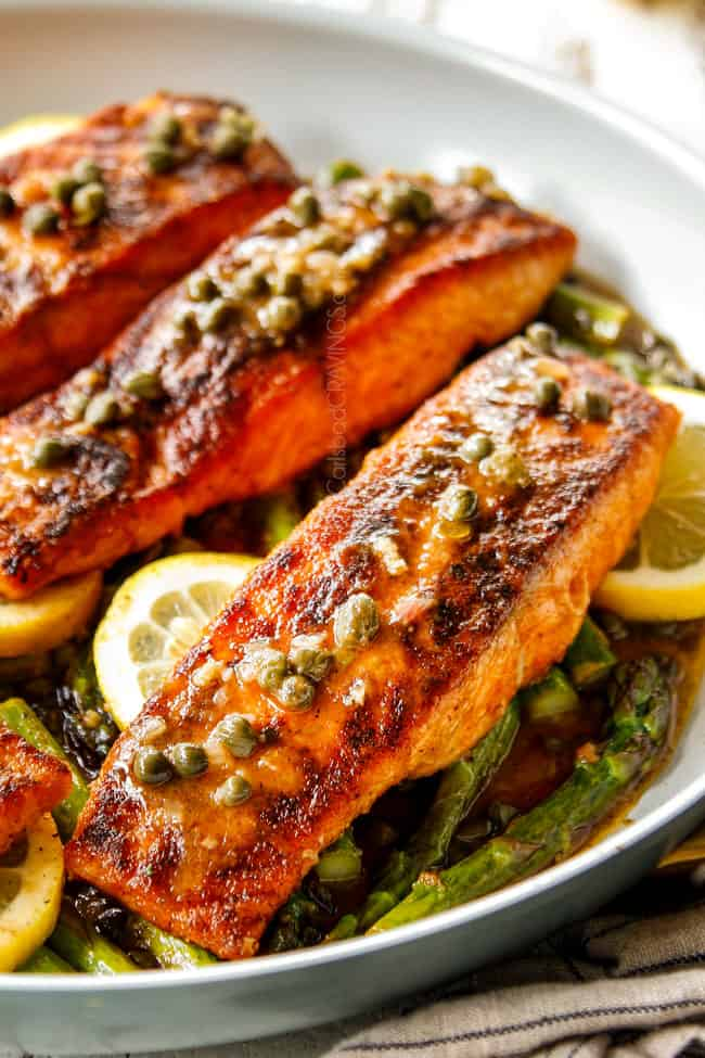 showing how to make lemon salmon and asparagus by spooning lemon butter sauce over salmon