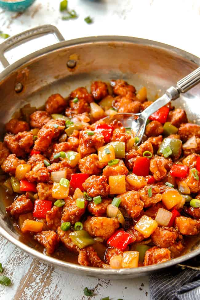 showing how to make Chinese Sweet and Sour Chicken recipe by by stirring chicken and and sweet and sour sauce