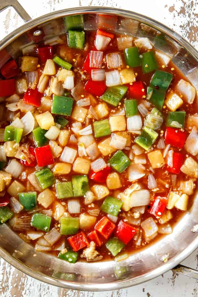 showing how to make sweet and sour chicken by adding sweet and sour sauce to vegetables and simmering until thickened