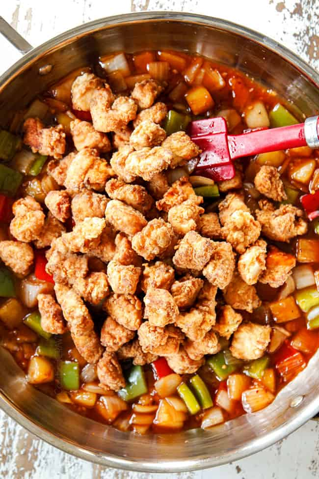 showing how to make sweet and sour chicken by adding breaded chicken to sauce