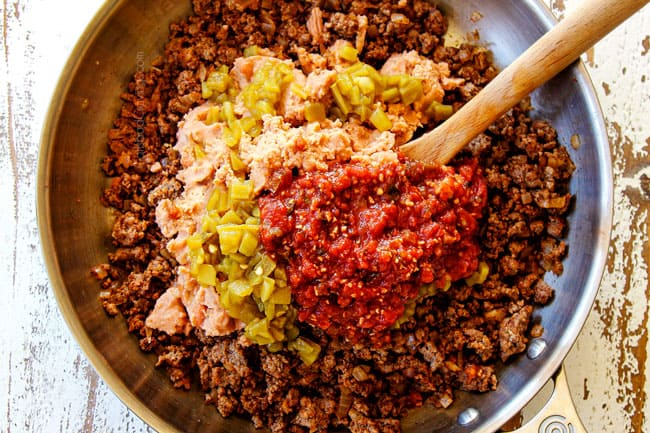 showing how to make tostada recipe by adding refried beans, salsa, and green chilies to ground beef