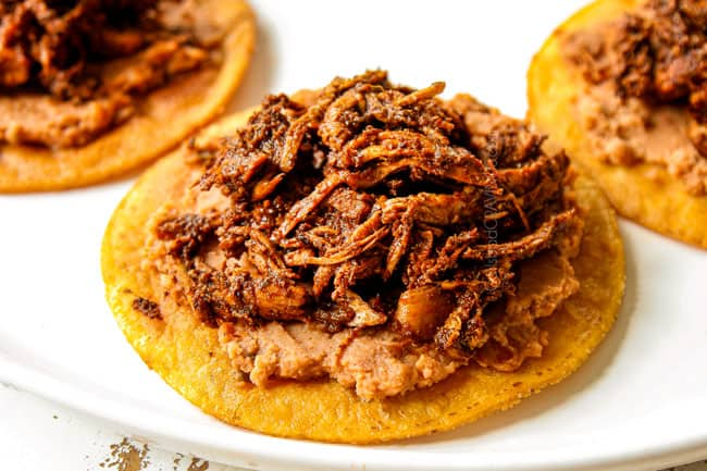 showing how to make chicken tostadas by layering tostada shells with refried beans and chicken