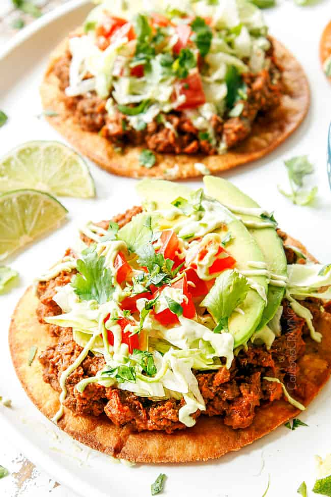 showing how to make best tostada recipe by topping tostada shell with refried beans, beef, lettuce, tomatoes, avocados and sour cream