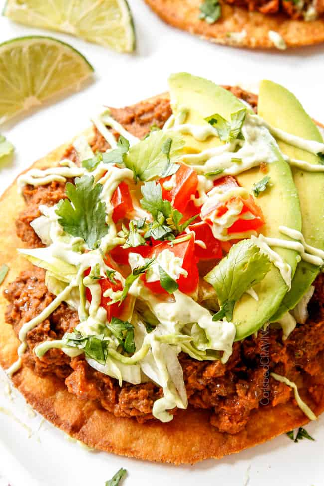 up close of tostada topped with beef, beans, lettuce and tomatoes to show how crisp the tostada shell is