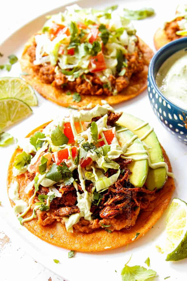 showing how to serve tostadas by lining on a platter and drizzling with avocado crema
