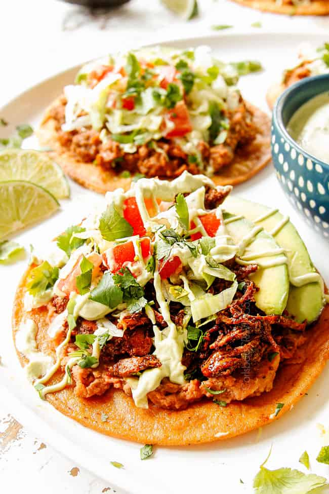showing how to make chicken tostadas by adding chicken tostada shells over beans