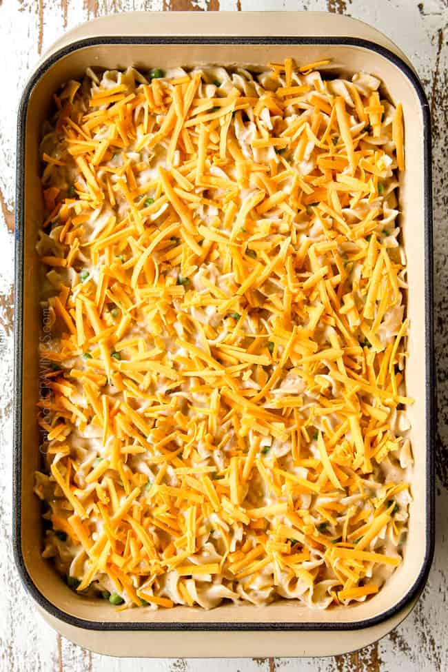 showing how to make Tuna Noodle Casserole by topping 9x13 baking dish with cheese