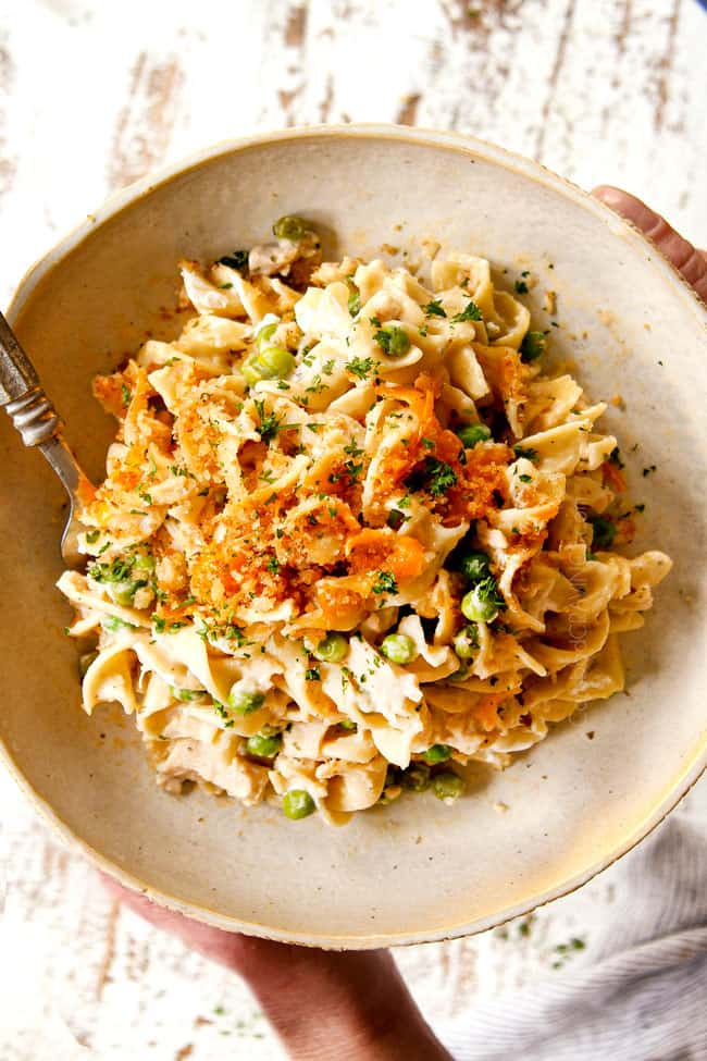showing how to serve Tuna  Casserole recipe by adding to a plate and garnishing with parsley