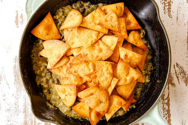 showing how to make Chilaquiles Verdes by adding crispy baked tortilla chips