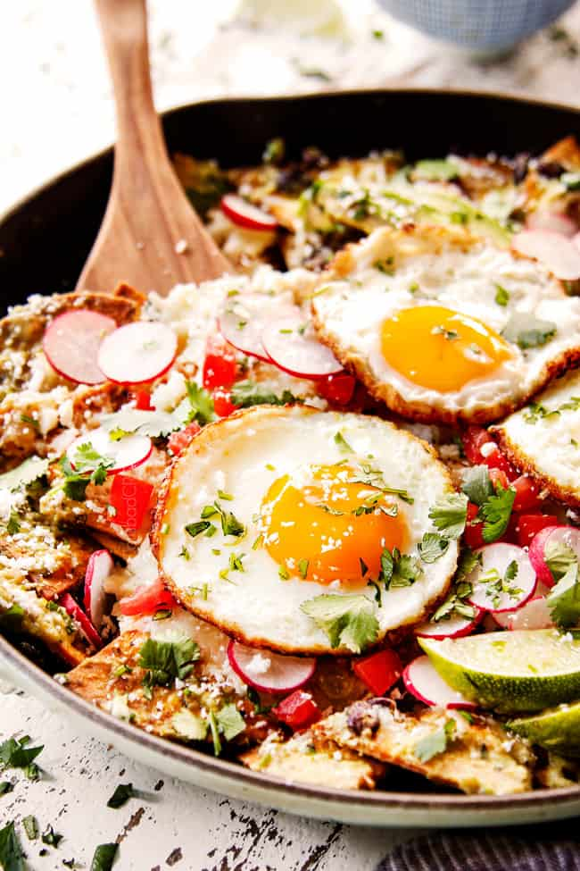 showing how to garnish Chilaquiles Rojos by topping with cilantro, queso fresco, radishes, fried eggs and sliced avocado