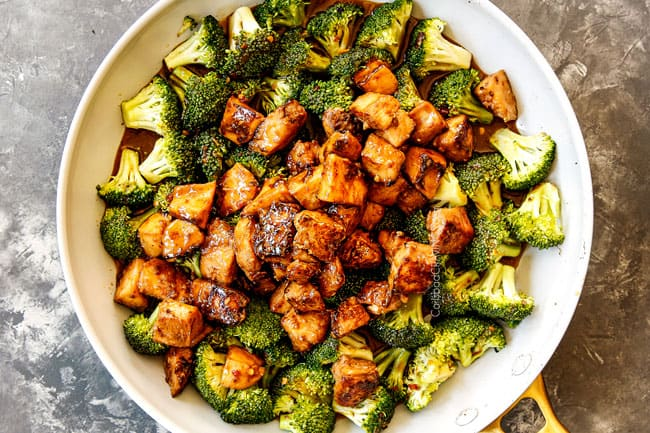 showing how to make Chinese Chicken and Broccoli recipe by adding chicken and stir fry sauce to broccoli in skillet
