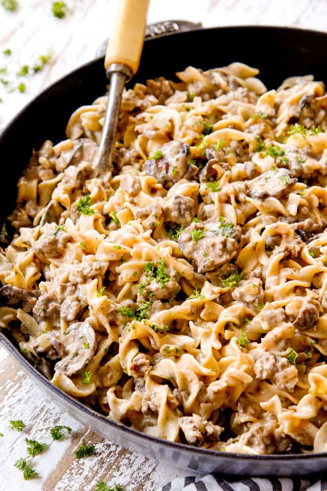 showing how to serve best ground beef stroganoff recipe by garnishing with parsley in a skillet