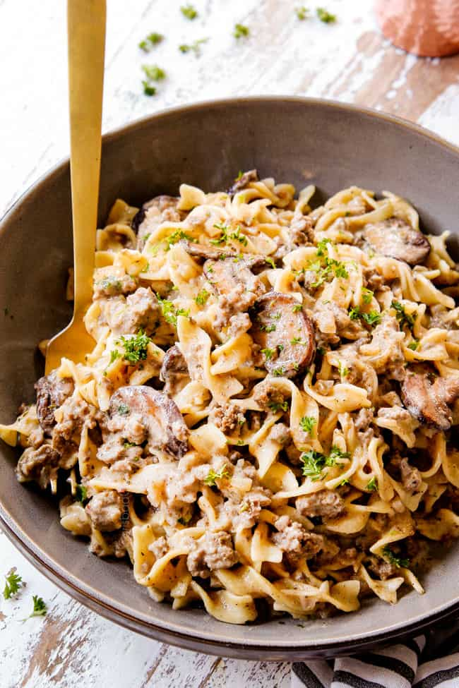 showing how to serve beef stroganoff with ground beef by placing in a bowl with egg noodles, garnished with parsley with a gold fork