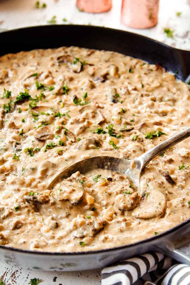 side view of a spoon in the ground beef stroganoff mushroom gravy showing how creamy it is