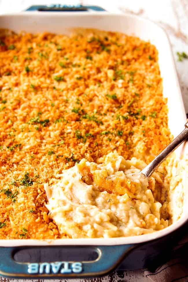 showing how creamy hash brown casserole recipe is by scooping a corner of the casserole