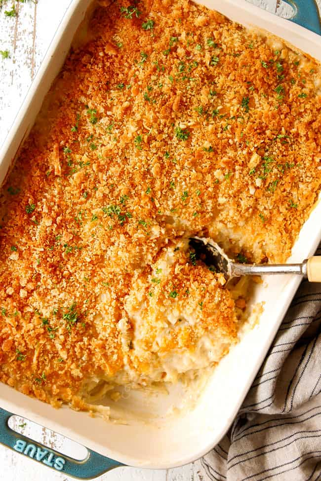 showing how to top easy hashbrown casserole by topping with crushed Ritz crackers