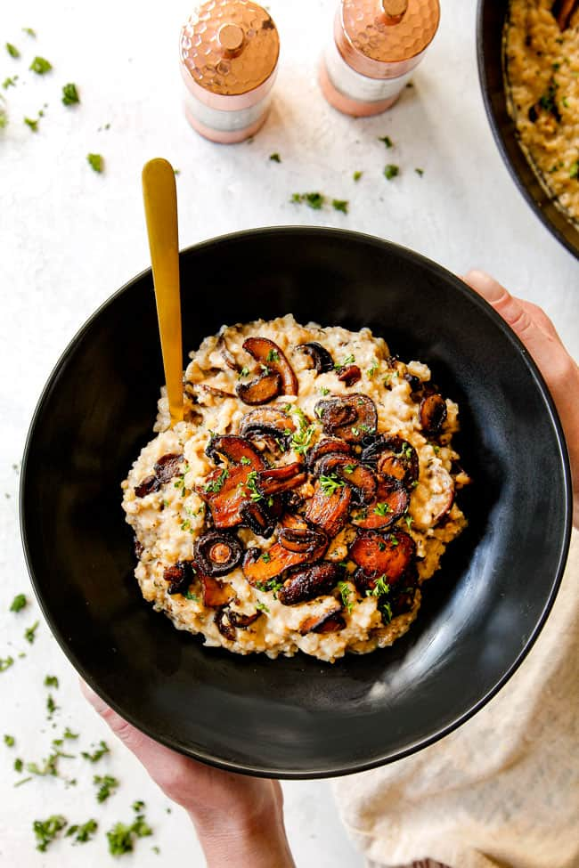 showing how to serve mushroom risotto recipe by adding to a small black bowl and garnishing with parsley