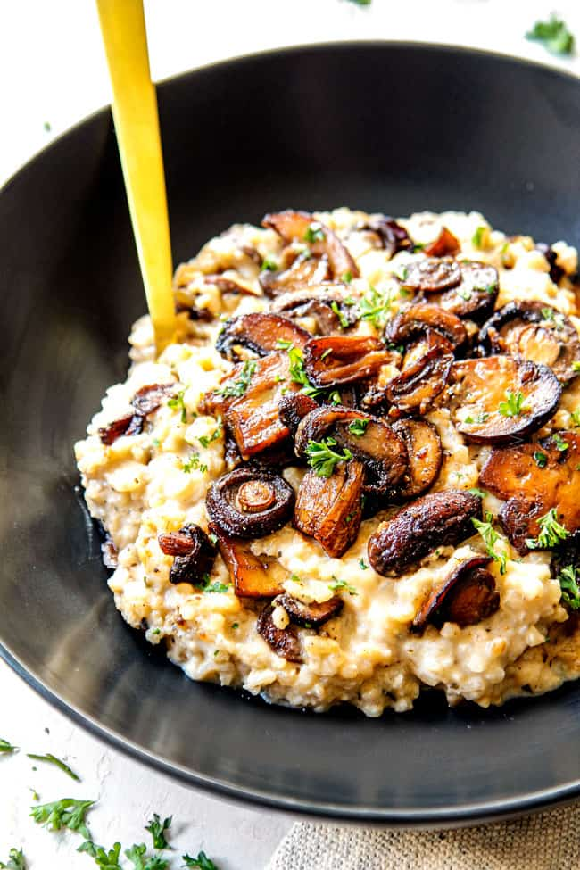 a bowl of easy mushroom risotto recipe garnished with mushrooms showing how deeply caramelized the mushrooms should look