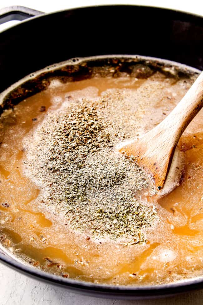 showing how to make mushroom risotto recipe by adding warm broth, salt, pepper, parsley, thyme to rice in black Dutch oven