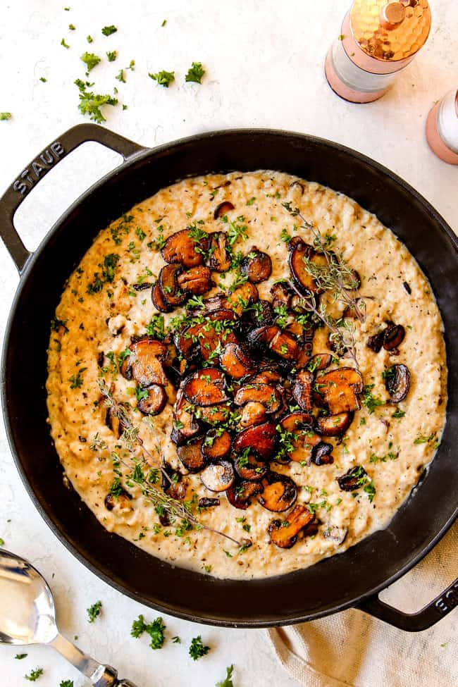 top view of mushroom risotto showing how to garnish with caramelized mushrooms, fresh thyme and fresh parsley
