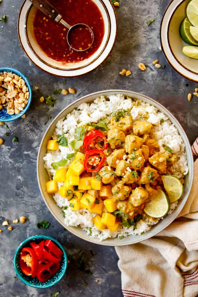 showing what to serve with Thai peanut chicken by showing chicken in a bowl over rice with garnish bowls of chili sauce, peanuts, limes