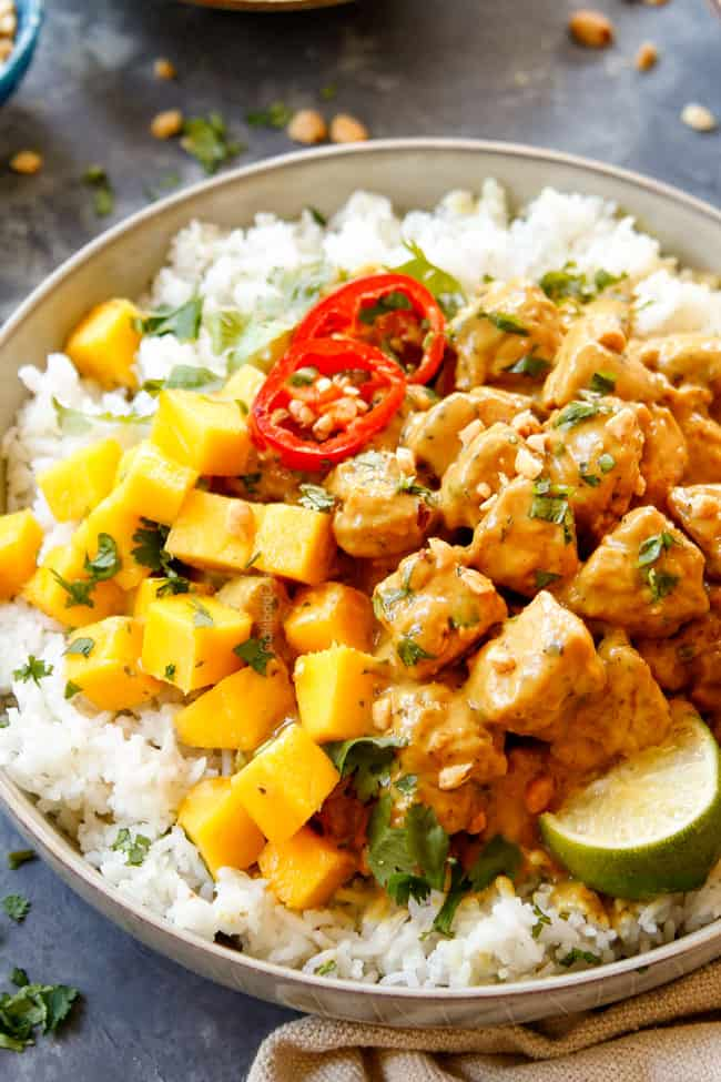 up close of Peanut Butter Sauce Chicken in a bowl with cilantro and mango