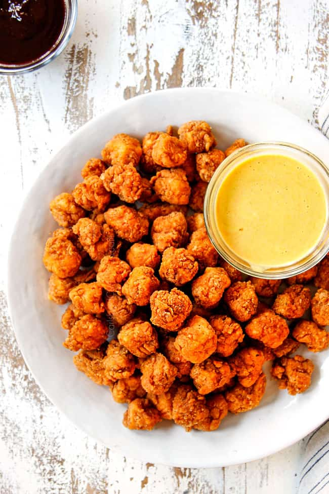 showing how to serve KFC Popcorn Chicken by placing on a white platter with honey mustard dip