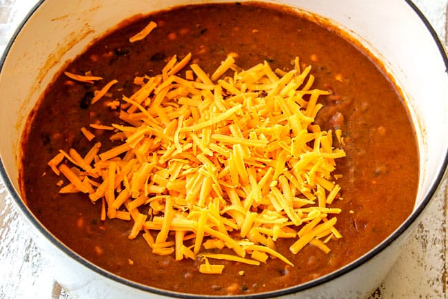 showing how to make cheesy Chicken Enchilada Soup by adding cheddar cheese to soup