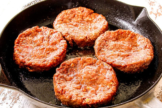 showing how to cook burgers on the stove by adding 4 patties to a cast iron skillet