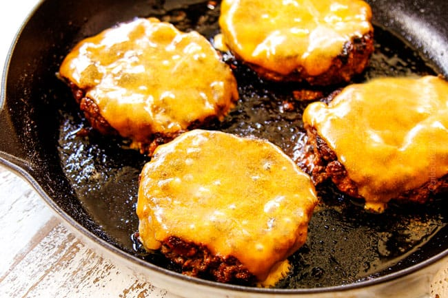 showing how to make burgers on the stove by topping each of the 4 patties with a slice of cheese