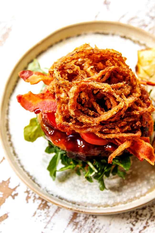 showing how to make BBQ burger recipe by stacking with bacon and fried onion strings