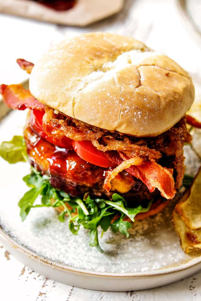showing how to serve BBQ burger recipe by layering buns with lettuce, hamburger, tomatoes, bacon and fried onion strings