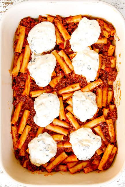 showing how to make Baked Ziti by recipe layering a 9x13 baking dish with ziti mixed with meat sauce followed by ricotta