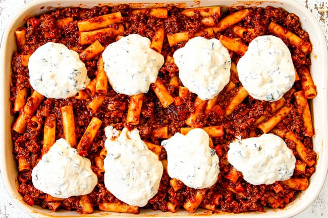 showing how to make best Baked Ziti with ricotta, Italian sausage and meat by topping with remaining ziti pasta and remaining ricotta
