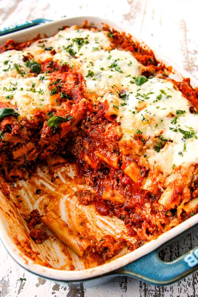 showing how saucy Baked Ziti with ricotta, Italian sausage and meat is by scooping away half of the pasta and showing the layers of noodles and sauce