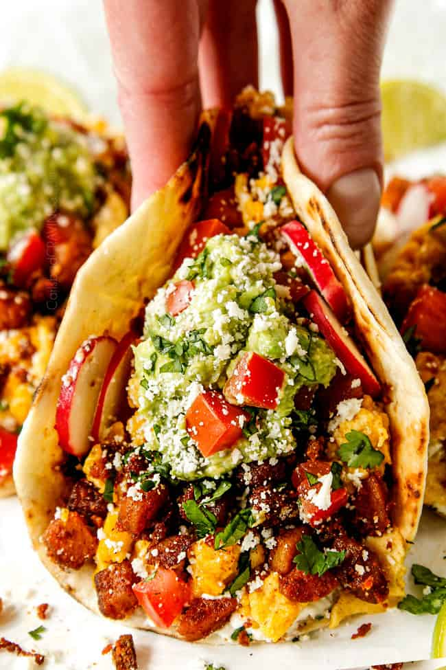 up close showing how to serve breakfast tacos by topping with guacamole and tomatoes