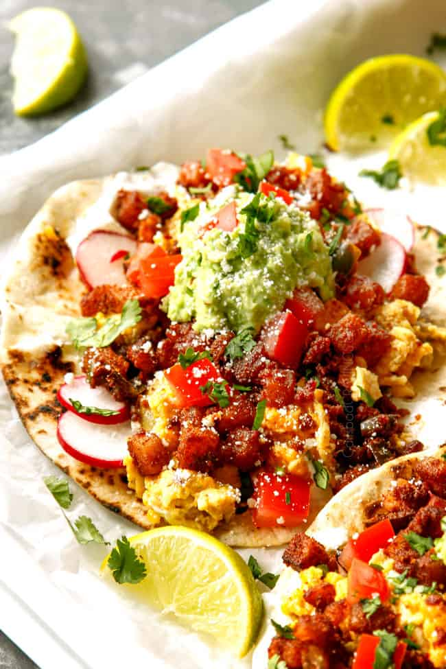 up close of breakfast tacos showing what to add to tortillas - scrambled eggs, chorzio and potatoes topped with avocados and tomatoes.