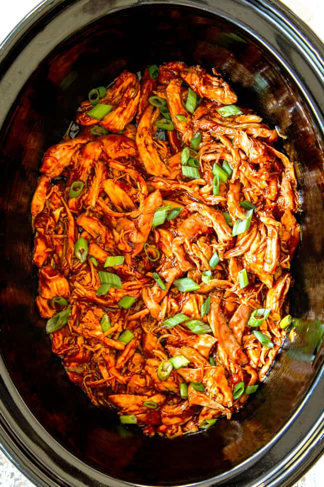 showing how to make slow cooker honey garlic chicken by shredding chicken in the crockpot