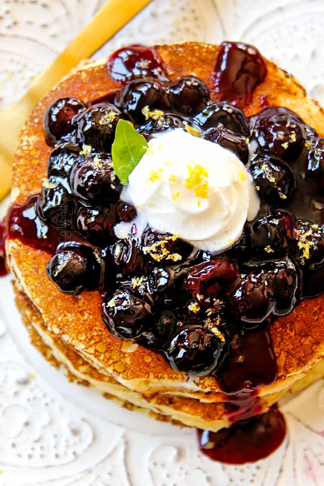top view showing how to serve lemon ricotta pancakes by stacking pancakes on a white plate with blueberry sauce and a dollop of whip cream