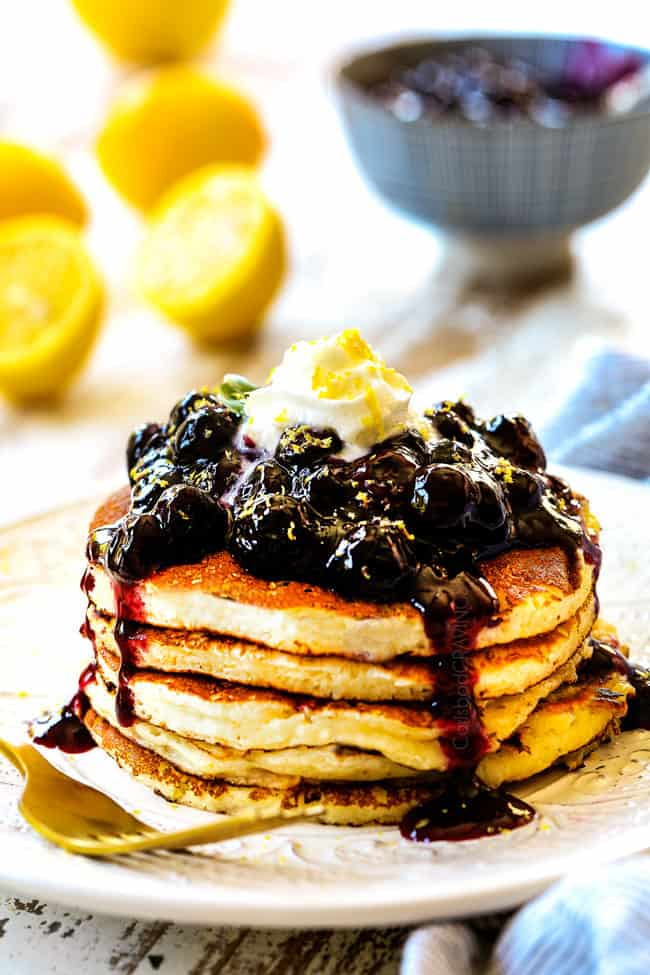 showing to serve lemon ricotta pancakes recipe by stacking pancakes on a white plate and topping with syrup