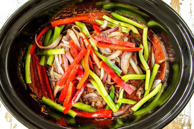 showing how to make Slow Cooker Ropa Vieja by adding beef, tomatoes, beef broth, oregano, cumin, onions and bell peppers to crockpot