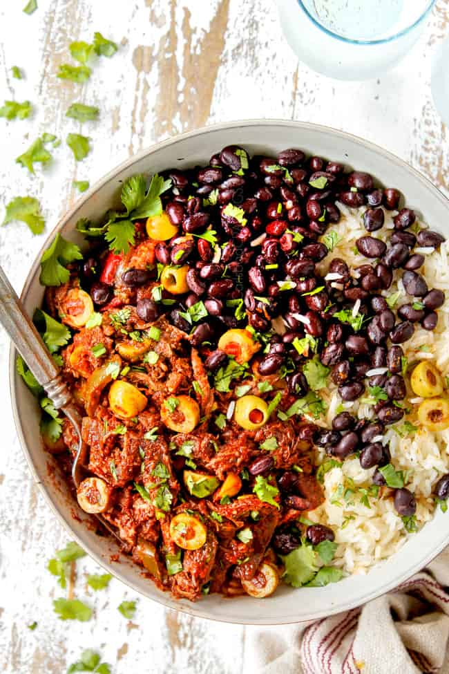 showing how to serve Ropa Vieja recipe by adding to a bowl with rice and beans and garnishing with cilantro