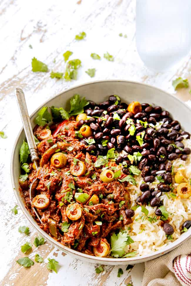 showing how to garish Cuban Ropa Vieja by adding cilantro and more Spanish olives to beef in a bowl with rice