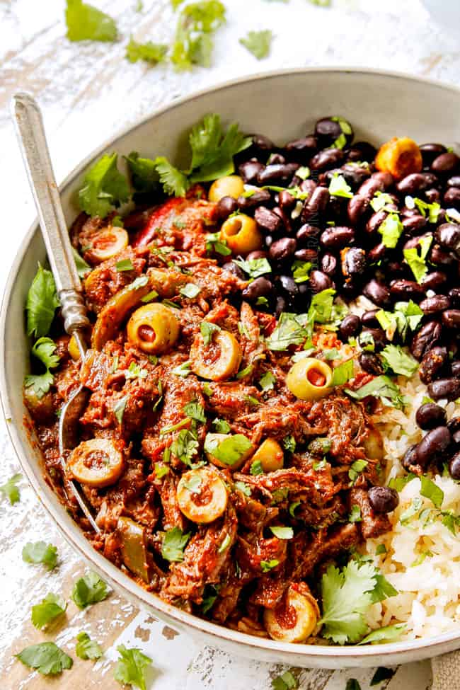 showing how to serve Slow cooker Ropa Vieja by adding to a bowl of rice and beans