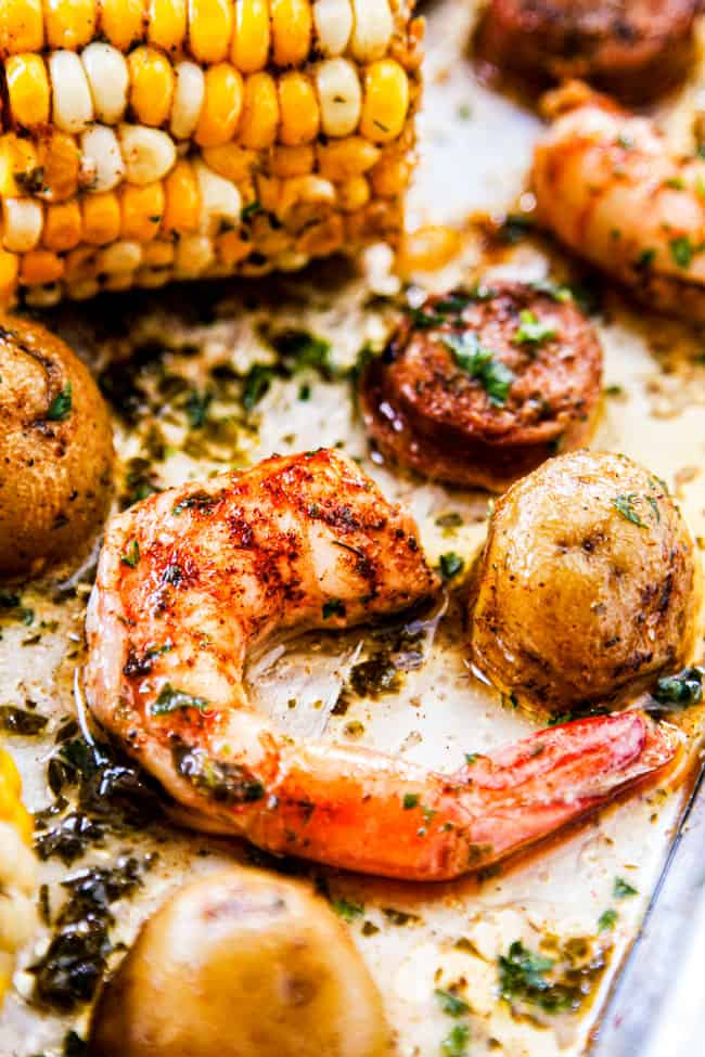 showing how to make sheet pan shrimp boil recipe with an up close shot of shrimp garnishing with parsley