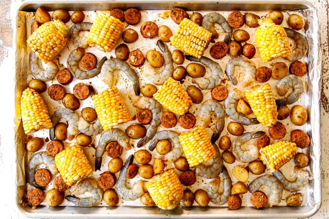 showing how to make sheet pan shrimp boil recipe by adding shrimp to baking sheet with corn, potatoes and sausage and spreading into an even layer